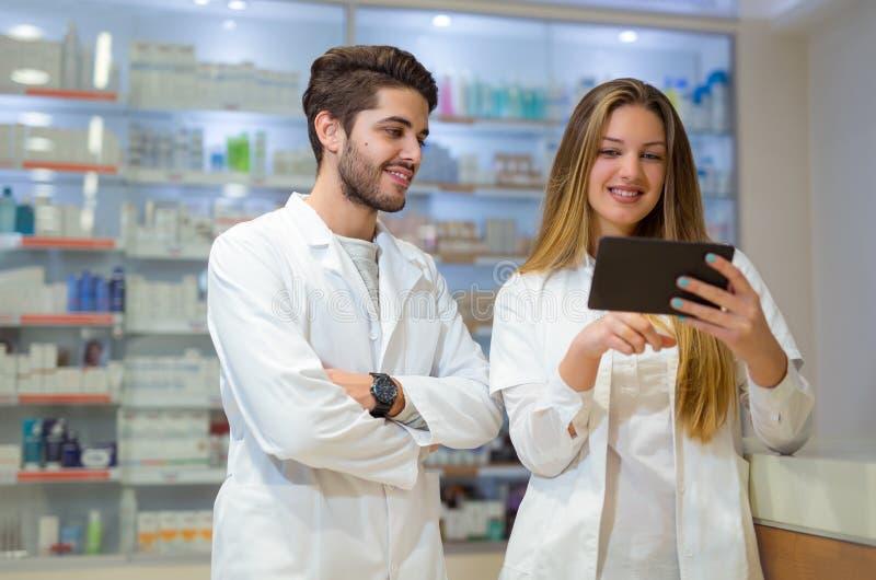 Φαρμακοποιοί που χρησιμοποιούν την ψηφιακή ταμπλέτα ελέγχοντας την ιατρική στοκ φωτογραφίες με δικαίωμα ελεύθερης χρήσης