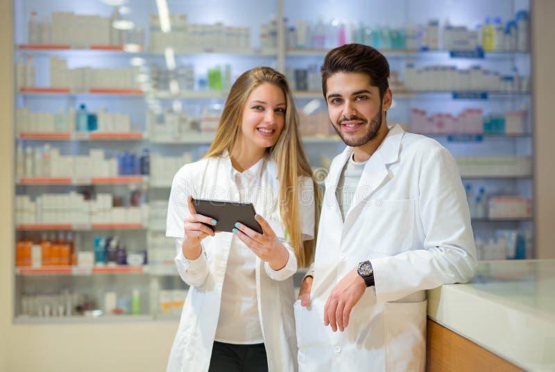 Φαρμακοποιοί που χρησιμοποιούν την ψηφιακή ταμπλέτα ελέγχοντας την ιατρική στοκ εικόνες