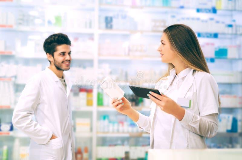 Φαρμακοποιοί που χρησιμοποιούν την ψηφιακή ταμπλέτα ελέγχοντας την ιατρική στοκ φωτογραφία
