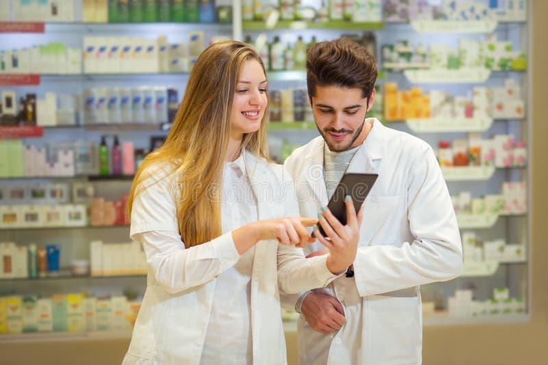 Φαρμακοποιοί που χρησιμοποιούν την ψηφιακή ταμπλέτα στοκ φωτογραφία