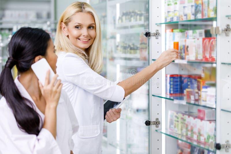 φαρμακοποιοί χρησιμοποιώντας τις ψηφιακές συσκευές και χαμογελώντας ο ένας τον άλλον στοκ φωτογραφία με δικαίωμα ελεύθερης χρήσης