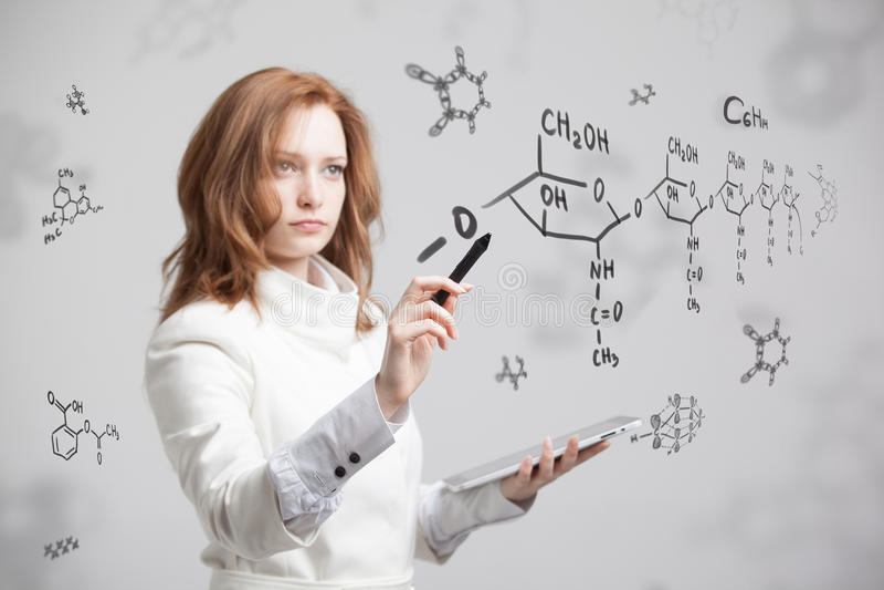 Φαρμακοποιός γυναικών που εργάζεται με τους χημικούς τύπους στο γκρίζο υπόβαθρο στοκ εικόνες με δικαίωμα ελεύθερης χρήσης