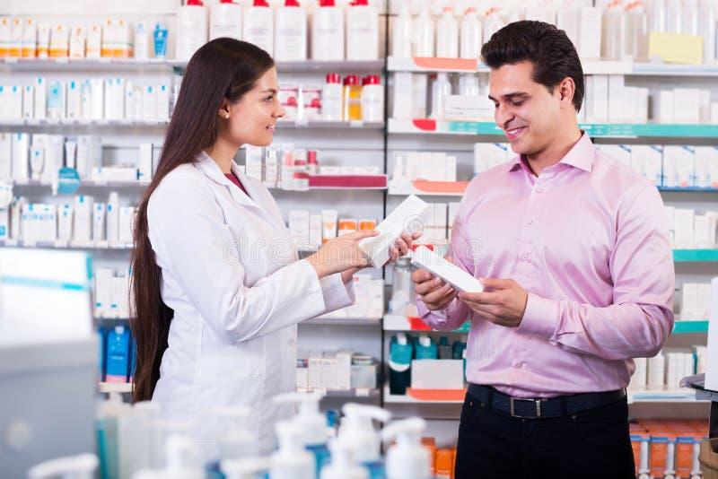 Φαρμακοποιός και συμβουλευτικό άτομο στο φαρμακείο στοκ εικόνα με δικαίωμα ελεύθερης χρήσης