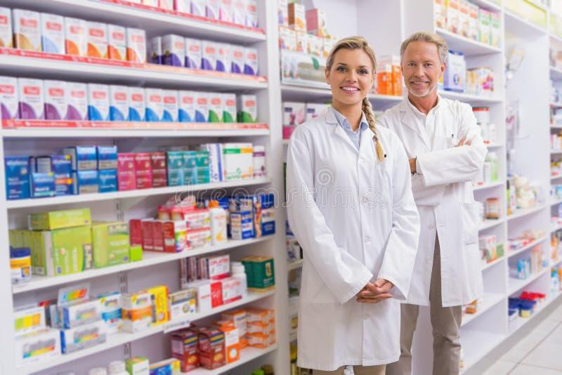 Φαρμακοποιός με τον εκπαιδευόμενό του που στέκεται και που χαμογελά στη κάμερα στοκ εικόνα