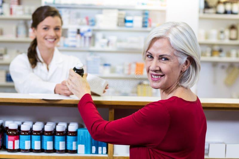 Φαρμακοποιός που δίνει την ιατρική στον πελάτη στο φαρμακείο στοκ φωτογραφίες με δικαίωμα ελεύθερης χρήσης