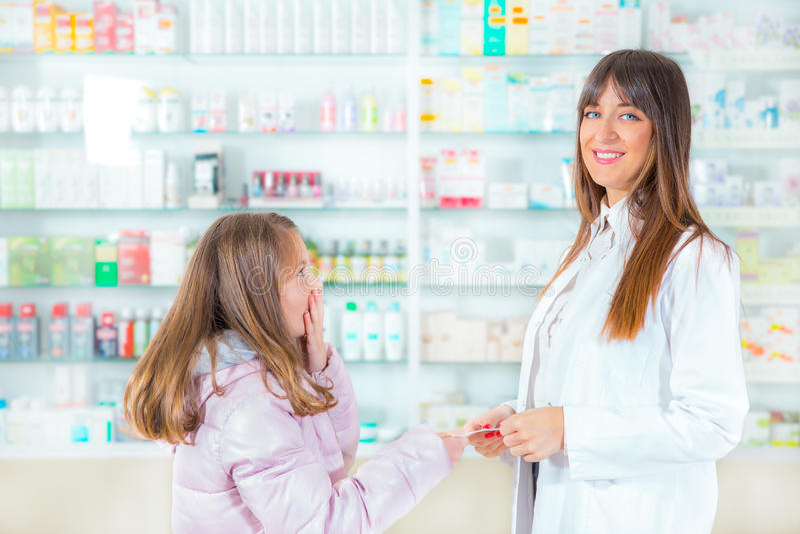 Φαρμακοποιός που δίνει τις βιταμίνες στο κορίτσι παιδιών στο φαρμακείο στοκ φωτογραφία