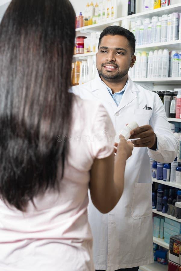 Φαρμακοποιός που δίνει το προϊόν στο θηλυκό πελάτη στο φαρμακείο στοκ φωτογραφίες