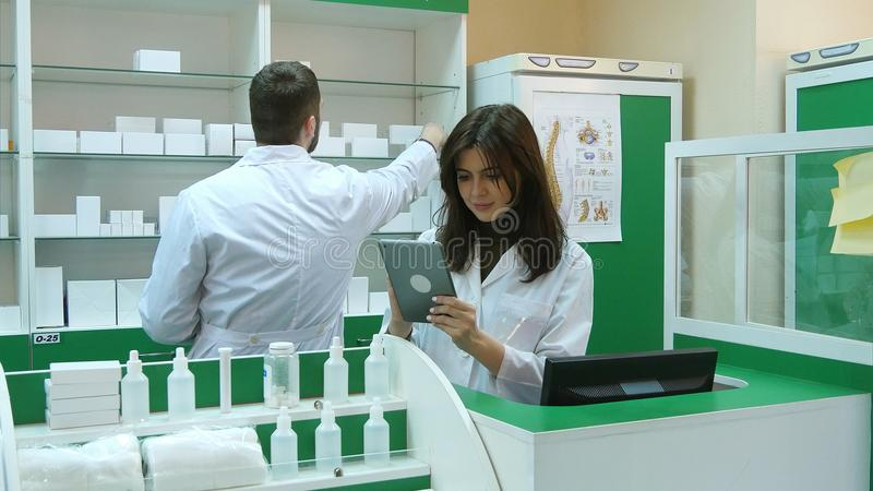 Φαρμακοποιός που απασχολείται με μια ταμπλέτα στην εκμετάλλευση φαρμακείων σε το στο χέρι της διαβάζοντας τις πληροφορίες στοκ εικόνες με δικαίωμα ελεύθερης χρήσης