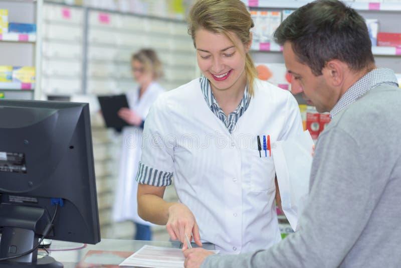 Φαρμακοποιός που βοηθά τον πελάτη στην αντίθετη θέση στοκ φωτογραφία με δικαίωμα ελεύθερης χρήσης