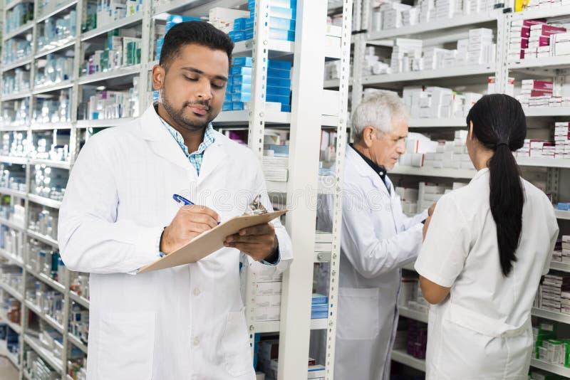 Φαρμακοποιός που γράφει στην περιοχή αποκομμάτων ενώ οι συνάδελφοι που αναμένουν τοποθετούν σε ράφι στοκ φωτογραφία