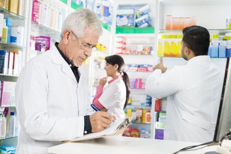 Φαρμακοποιός που γράφει στην περιοχή αποκομμάτων ενώ συνάδελφοι που εργάζονται στο φαρμακείο στοκ εικόνες