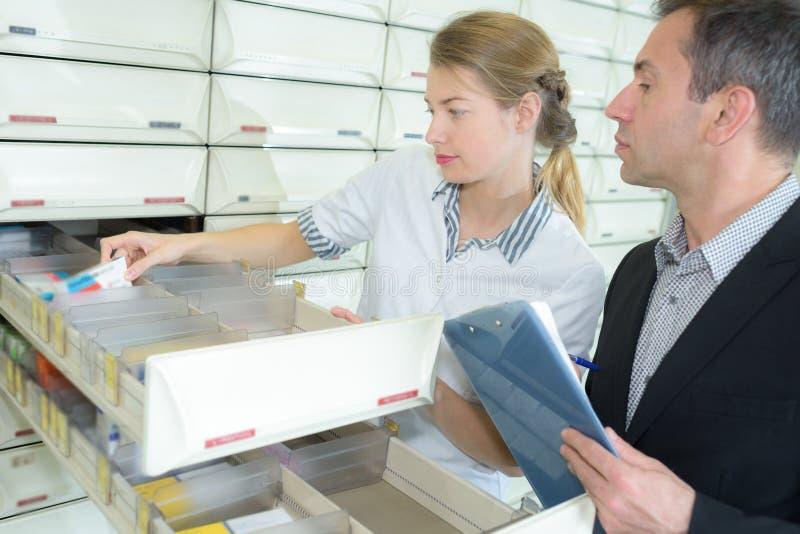 Φαρμακοποιός που εξετάζει τη συσκευασία ιατρικής στο φαρμακείο στοκ φωτογραφίες με δικαίωμα ελεύθερης χρήσης