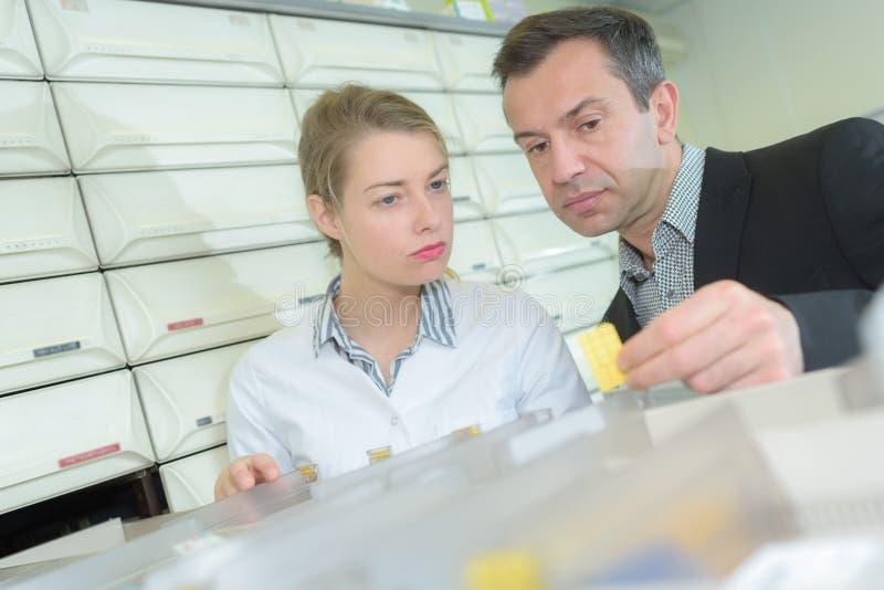 Φαρμακοποιός που εξετάζει το εμπορευματοκιβώτιο συνταγών και ιατρικής στο φαρμακείο στοκ φωτογραφία με δικαίωμα ελεύθερης χρήσης