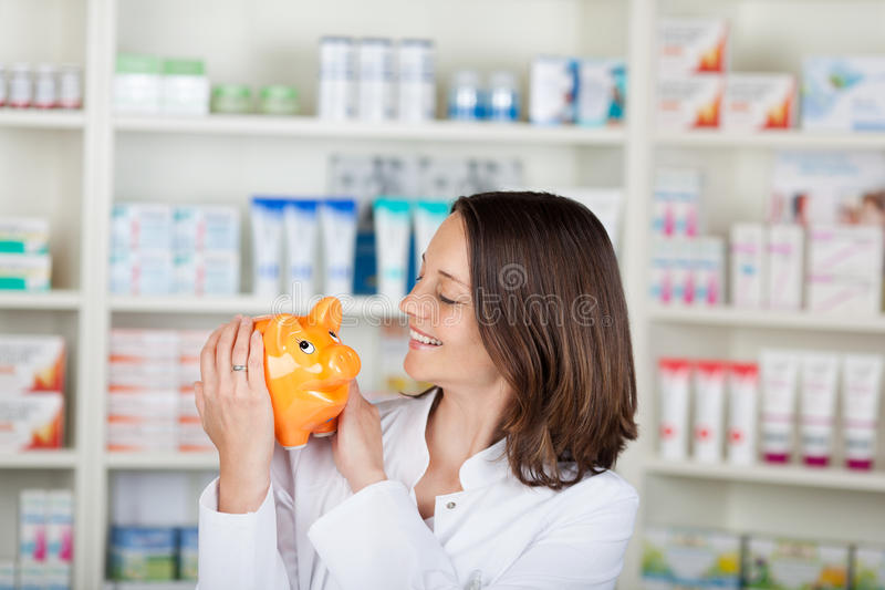 Φαρμακοποιός που εξετάζει Piggybank στο φαρμακείο στοκ φωτογραφίες με δικαίωμα ελεύθερης χρήσης