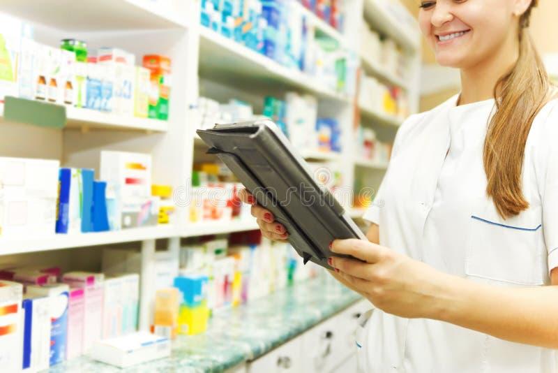 Φαρμακοποιός που εργάζεται με έναν υπολογιστή ταμπλετών στο φαρμακείο στοκ εικόνες
