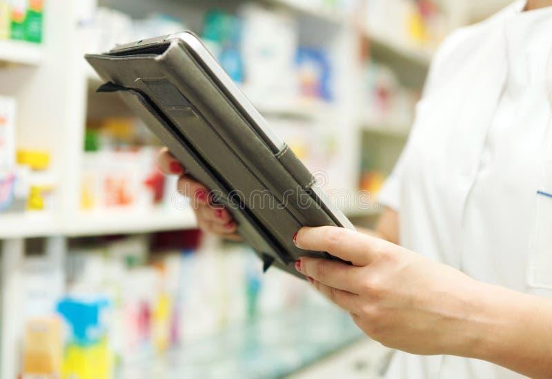 Φαρμακοποιός που εργάζεται με ένα PC ταμπλετών στο φαρμακείο στοκ εικόνες