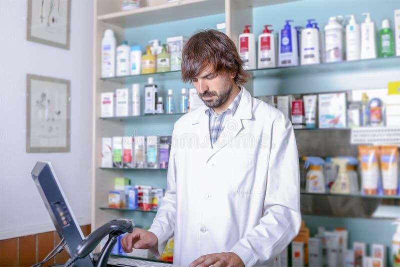 Φαρμακοποιός που εργάζεται με τον υπολογιστή στοκ εικόνα με δικαίωμα ελεύθερης χρήσης