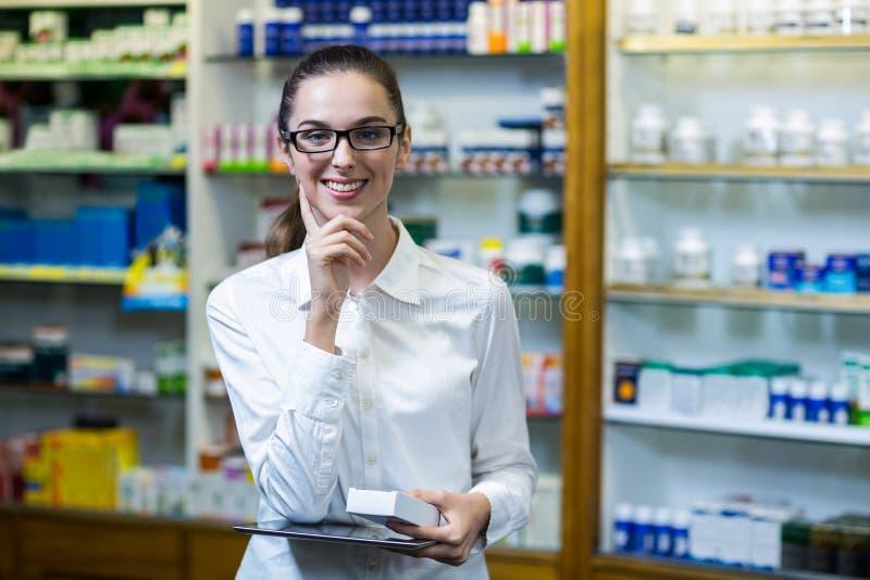 Φαρμακοποιός που κρατά την ψηφιακές ταμπλέτα και την ιατρική στο φαρμακείο στοκ φωτογραφία