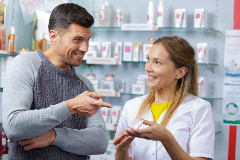 Φαρμακοποιός που μιλά στον αρσενικό πελάτη στοκ φωτογραφίες με δικαίωμα ελεύθερης χρήσης