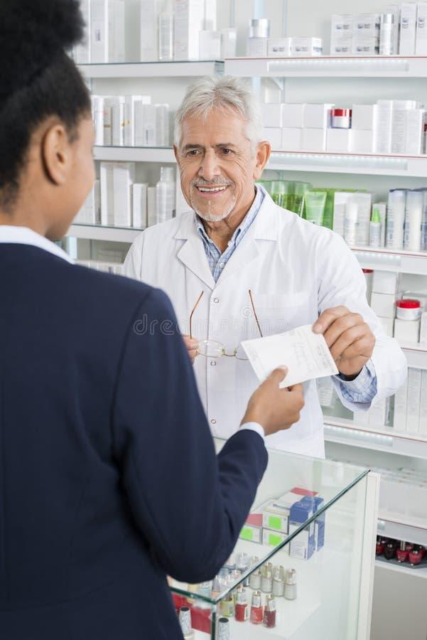 Φαρμακοποιός που παίρνει το έγγραφο συνταγών από τη επιχειρηματία στοκ φωτογραφίες με δικαίωμα ελεύθερης χρήσης