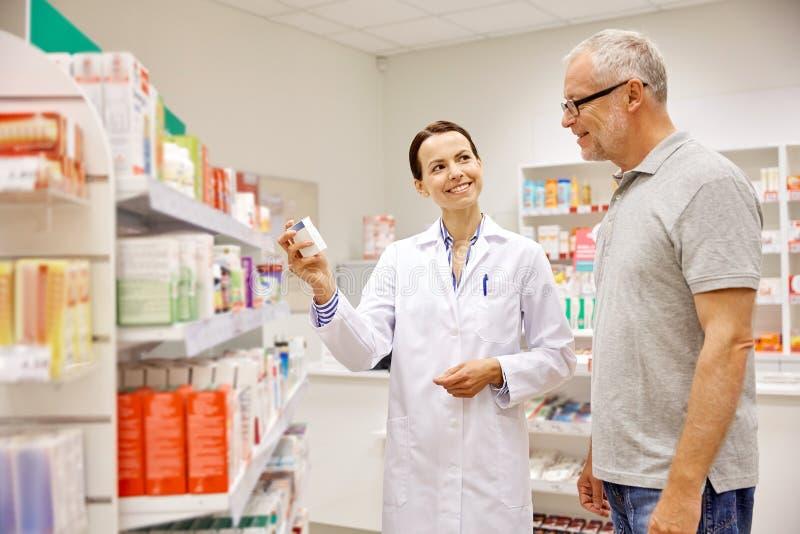 Φαρμακοποιός που παρουσιάζει φάρμακο στο ανώτερο άτομο στο φαρμακείο στοκ εικόνα με δικαίωμα ελεύθερης χρήσης