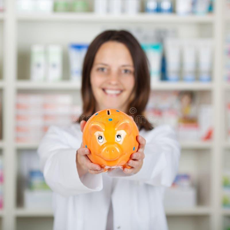 Φαρμακοποιός που παρουσιάζει Piggybank στο φαρμακείο στοκ φωτογραφίες με δικαίωμα ελεύθερης χρήσης