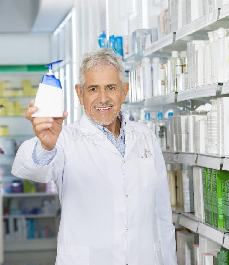 Φαρμακοποιός που χαμογελά ενώ διανομέας σαπουνιών εκμετάλλευσης στοκ εικόνα