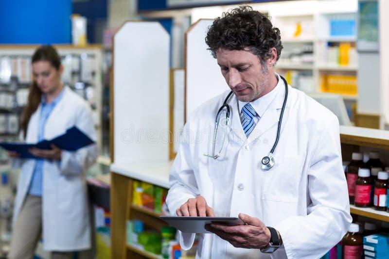 Φαρμακοποιός που χρησιμοποιεί την ψηφιακή ταμπλέτα στοκ εικόνες
