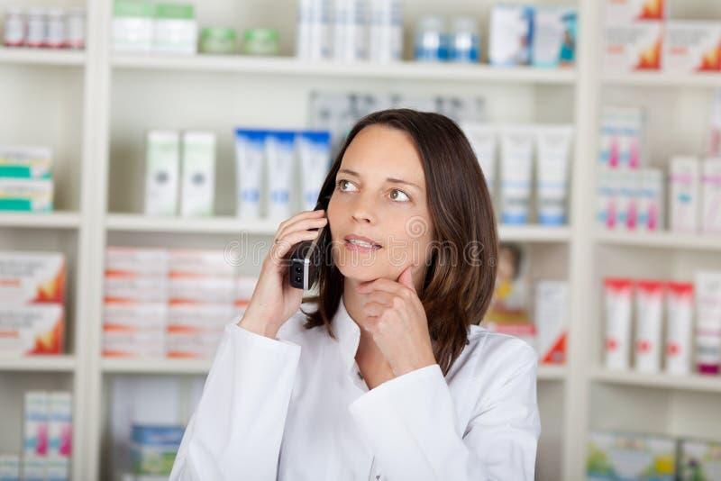 Φαρμακοποιός που χρησιμοποιεί το ασύρματο τηλέφωνο στοκ εικόνα