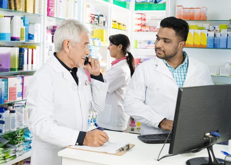 Φαρμακοποιός που χρησιμοποιεί το τηλέφωνο εξετάζοντας τους συναδέλφους που χρησιμοποιούν τον υπολογιστή στοκ εικόνα με δικαίωμα ελεύθερης χρήσης