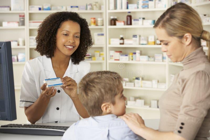 Φαρμακοποιός στο φαρμακείο με τη μητέρα και το παιδί στοκ φωτογραφίες με δικαίωμα ελεύθερης χρήσης