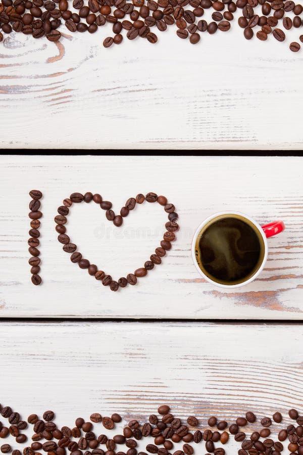 Φασόλια καφέ και κόκκινη κούπα που χρησιμοποιείται για να συλλαβίσει την αγάπη στοκ εικόνες