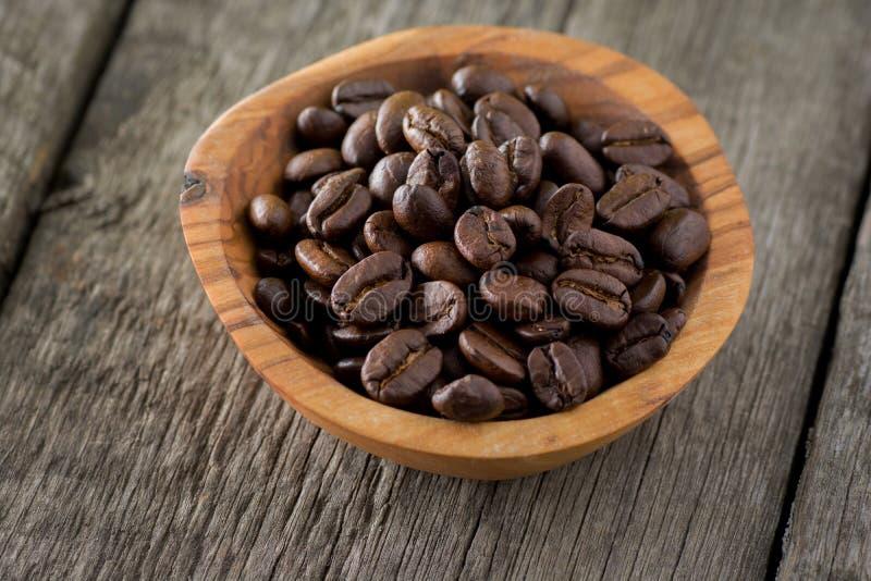 Φασόλια καφέ στο ξύλινο κύπελλο στο ξύλινο υπόβαθρο Εκλεκτική εστίαση στοκ εικόνες