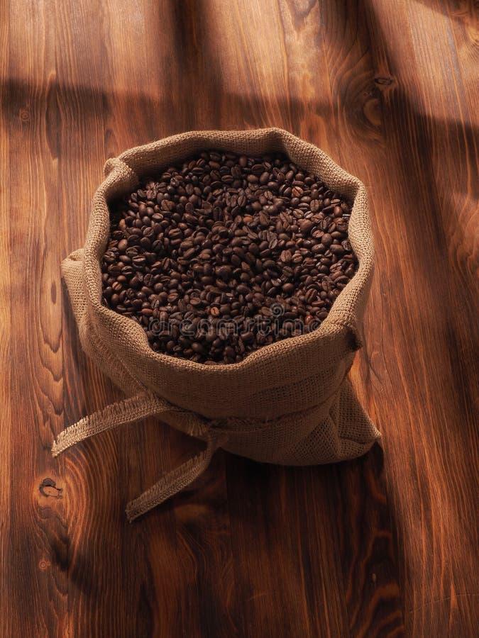 Φασόλι καφέ sackcloth στην τσάντα στο ξύλινο υπόβαθρο στοκ εικόνα με δικαίωμα ελεύθερης χρήσης