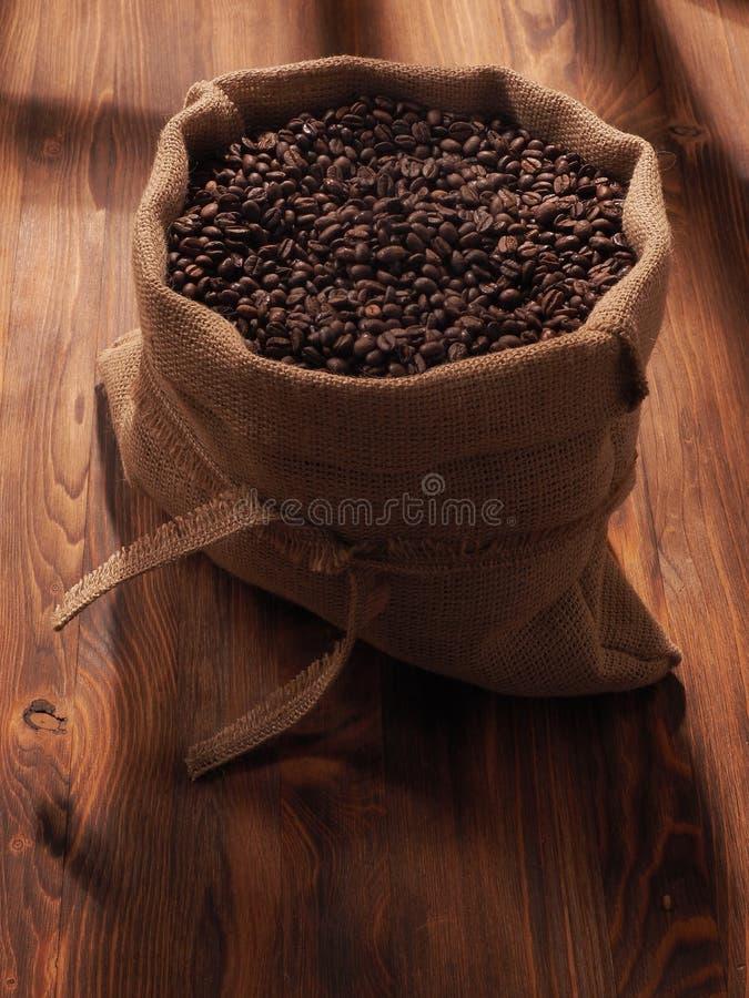 Φασόλι καφέ sackcloth στην τσάντα στο ξύλινο υπόβαθρο στοκ εικόνες με δικαίωμα ελεύθερης χρήσης