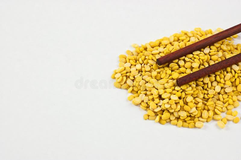 Φασόλια, κίτρινα σε ένα άσπρο υπόβαθρο και chopsticks στοκ φωτογραφίες