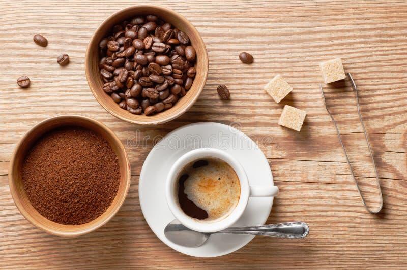 Φασόλια καφέ, επίγειος καφές και φλιτζάνι του καφέ στον ξύλινο πίνακα με τον εξοπλισμό και τα συστατικά, τοπ άποψη στοκ εικόνα