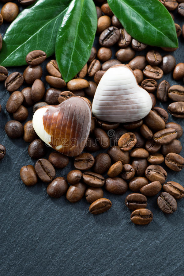 Φασόλια καφέ και καραμέλες σοκολάτας σε μια μορφή καρδιών στο σκοτάδι στοκ εικόνα με δικαίωμα ελεύθερης χρήσης