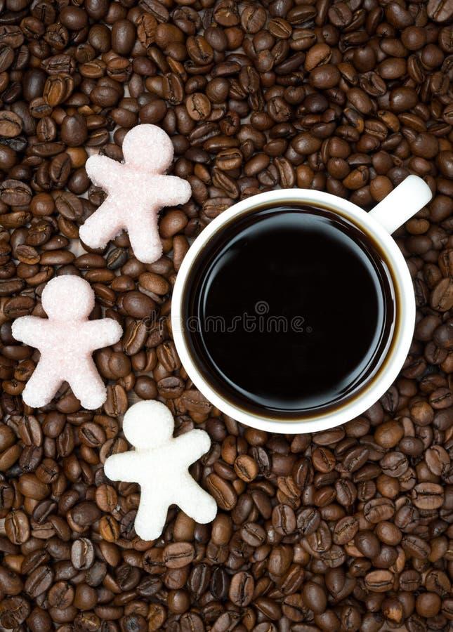 Φασόλια καφέ με το φλιτζάνι του καφέ και τη ζάχαρη υπό μορφή μικρών ατόμων στοκ φωτογραφία με δικαίωμα ελεύθερης χρήσης
