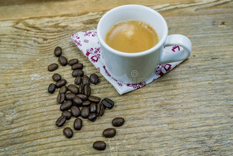 Φασόλια καφέ παράλληλα με ένα φλυτζάνι του καφέ γάλακτος στοκ φωτογραφία