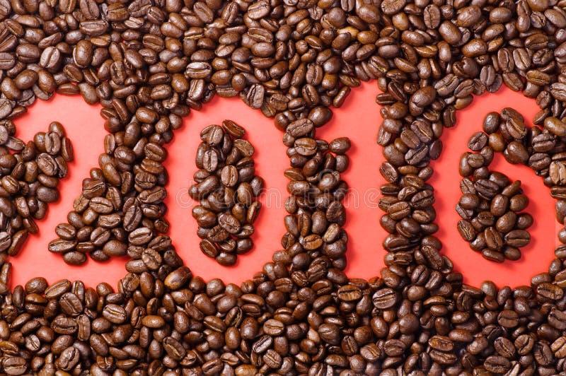 Φασόλια καφέ που διασκορπίζονται σε κόκκινο χαρτί με το συρμένο αριθμό 2016 στοκ φωτογραφίες