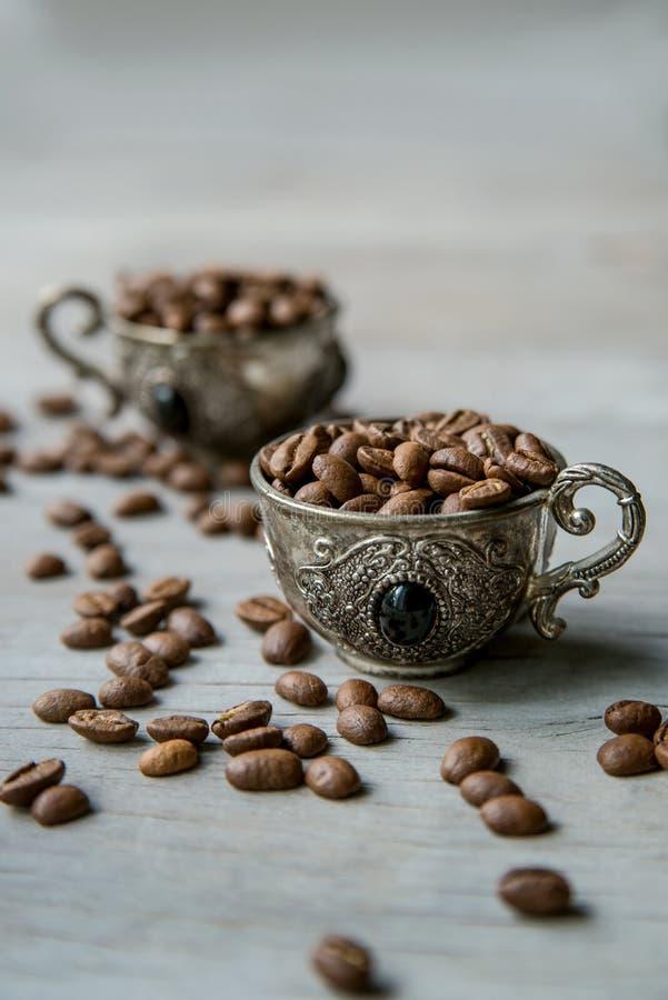 Φασόλια καφέ στα αραβικά ασημένια εκλεκτής ποιότητας κύπελλα στο ξύλινο υπόβαθρο στοκ εικόνες με δικαίωμα ελεύθερης χρήσης