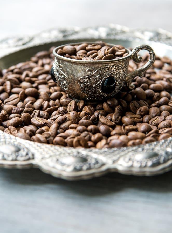 Φασόλια καφέ στα ασημένια εκλεκτής ποιότητας φλυτζάνια στο ξύλινο υπόβαθρο στοκ εικόνα με δικαίωμα ελεύθερης χρήσης