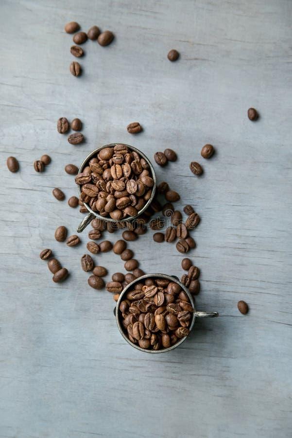 Φασόλια καφέ στα ασημένια εκλεκτής ποιότητας φλυτζάνια στο ξύλινο υπόβαθρο στοκ εικόνα