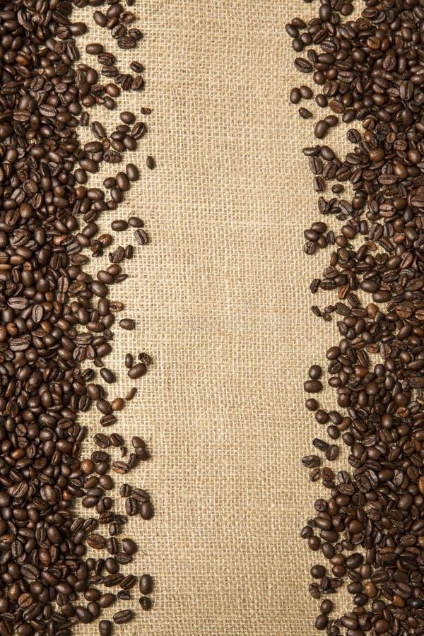 Φασόλια καφέ στο υπόβαθρο των υφασμάτων γιούτας στοκ φωτογραφία