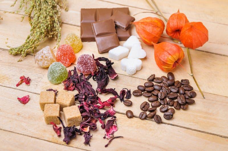 Φασόλια καφέ, hibiscus τσάι, ζάχαρη κομματιών, σοκολάτα και μαρμελάδα στοκ φωτογραφία