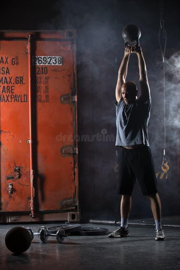 Φαλακρός χαρισματικός αθλητής που κάνει kettlebell την ταλάντευση στοκ εικόνες