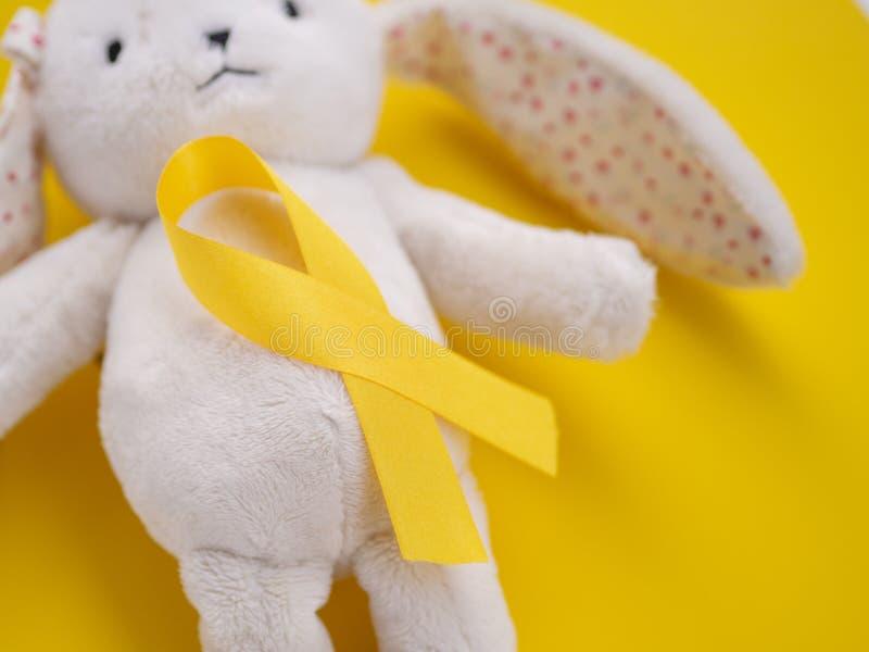 Φεβρουάριος, 15 Ακόμα ζωηρό λαγό με μια χρυσή κορδέλα σε κίτρινο φόντο Έννοια της ημέρας ευαισθητοποίησης για τον καρκίνο στην πα στοκ φωτογραφία με δικαίωμα ελεύθερης χρήσης