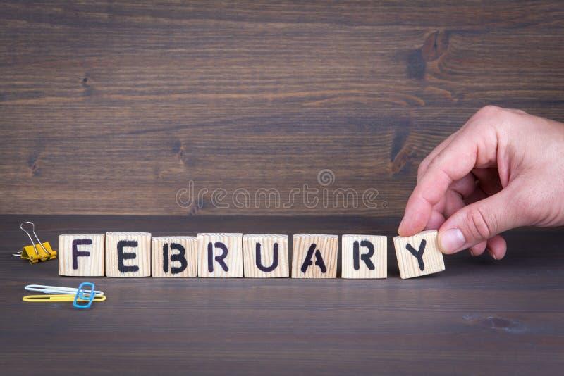 Φεβρουάριος Ξύλινες επιστολές στο πληροφοριακού και επικοινωνίας υπόβαθρο γραφείων γραφείων, στοκ εικόνα με δικαίωμα ελεύθερης χρήσης