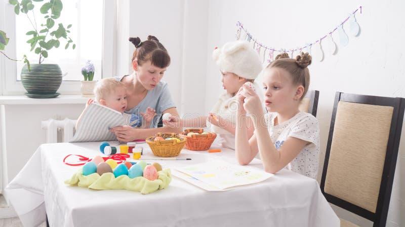 Φεστιβάλ Πάσχας: Η οικογένεια στον πίνακα προετοιμάζεται για τις διακοπές Η κόρη έβαλε ένα σχέδιο στο αυγό στοκ εικόνες